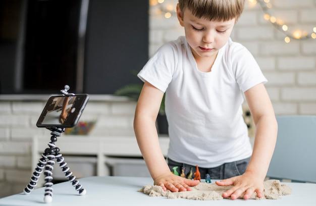 Criança de tiro médio brincando com areia Foto gratuita