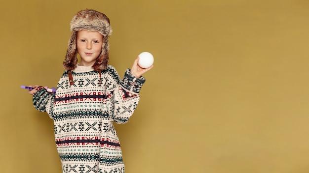 Criança de tiro médio com bola de neve e cópia-espaço Foto gratuita