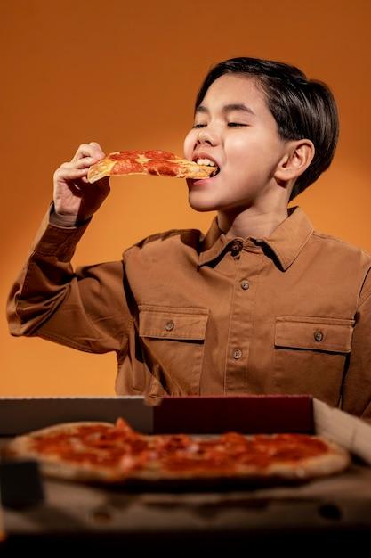 Criança de tiro médio comendo pizza Foto gratuita