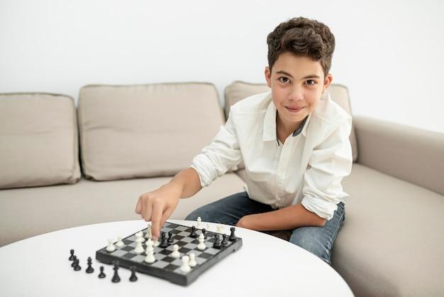 Criança de vista frontal sorridente jogando xadrez Foto gratuita