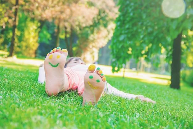 Criança deitada na grama verde. garoto se divertindo ao ar livre no parque primavera. Foto Premium