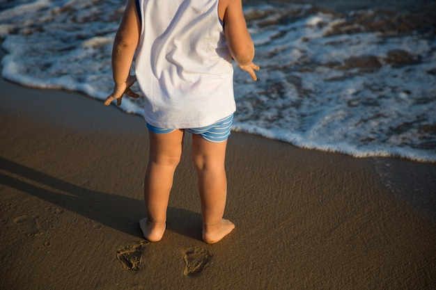 Criança descalça pelo mar Foto Premium