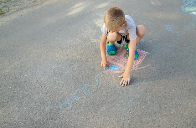 Criança desenha uma casa com giz na calçada Foto Premium