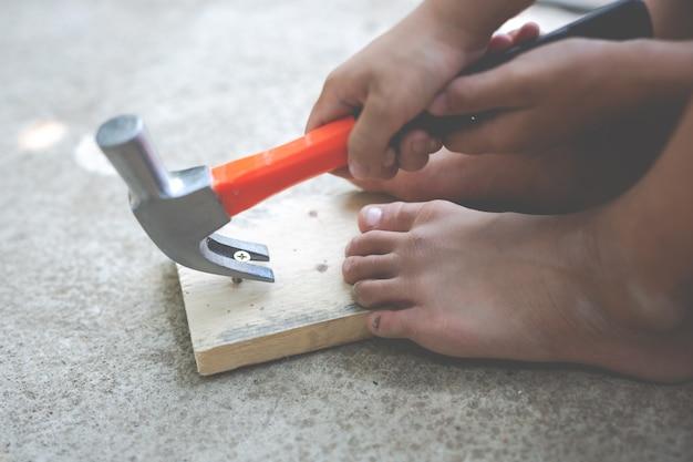 Criança do menino que prende uma ferramenta do martelo. Foto gratuita
