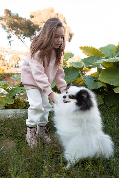 Criança do sexo feminino e cachorro fofinho brincando Foto gratuita