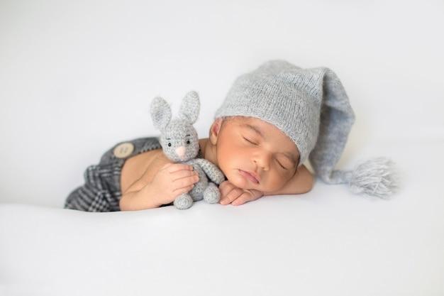 Criança dormindo com giro chapéu cinza e com coelho de brinquedo nas mãos Foto gratuita