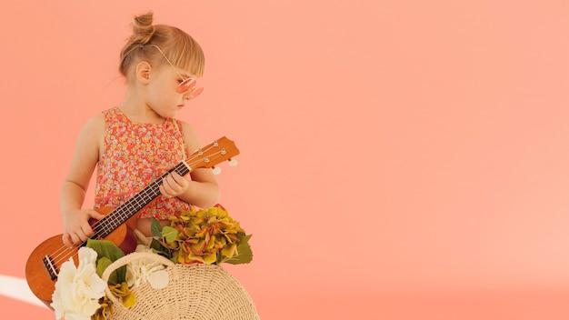 Criança elegante, segurando o violão Foto gratuita