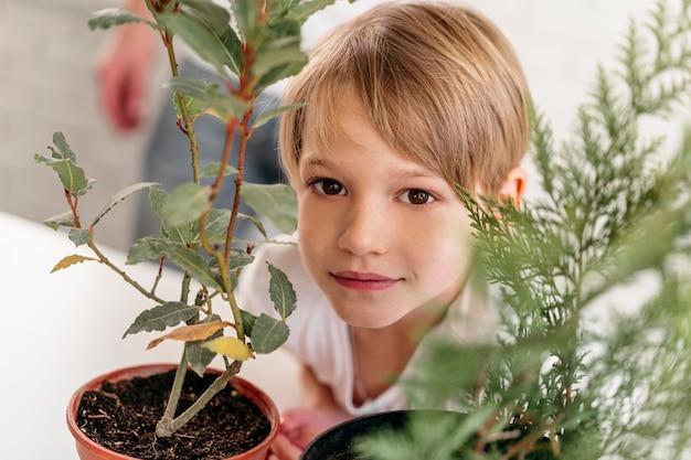 Criança em casa ao lado de plantas Foto gratuita