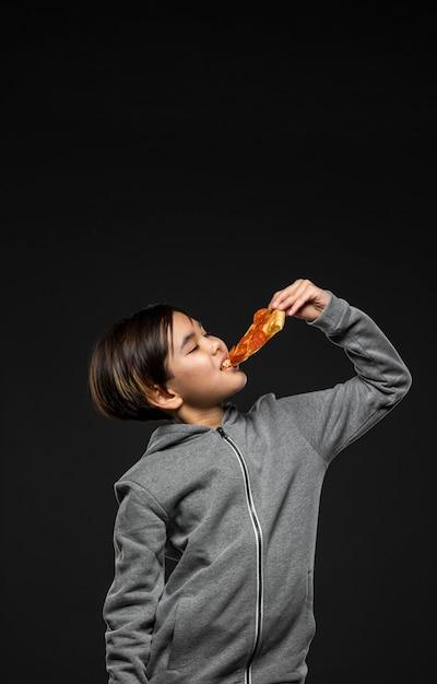 Criança em cena média comendo pizza com cópia-espaço Foto gratuita