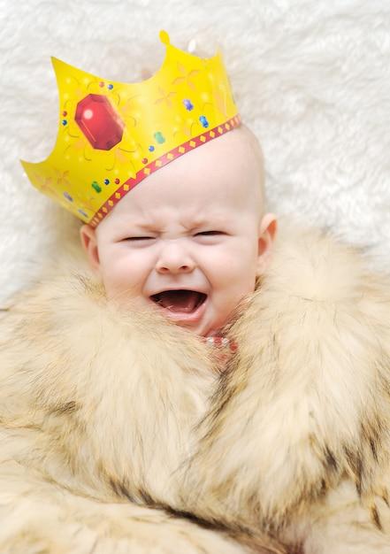 Criança em um cabo da pele e coroa em um fundo branco. bebê chorando Foto Premium