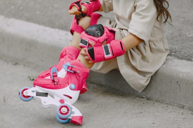 Criança em um parque de verão. garoto com um capacete rosa. menina com um rolo. Foto gratuita