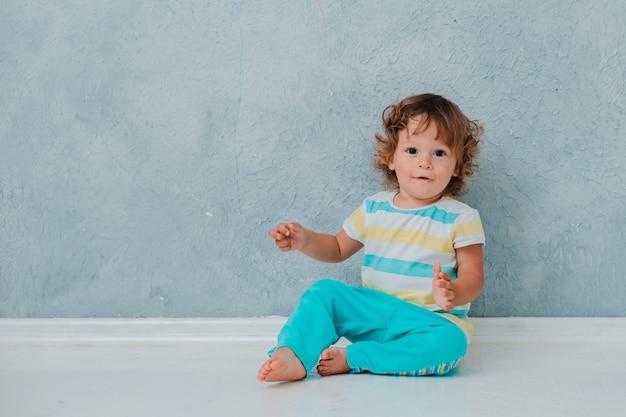 Criança encaracolada bonita engraçada senta-se jogando no carro em um piso branco no fundo da parede cinza. Foto Premium