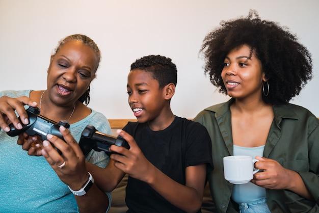 Criança ensinando a avó e a mãe a jogar videogame. Foto gratuita