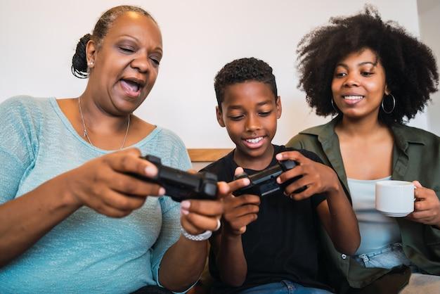 Criança ensinando avó e mãe para jogar videogame. Foto gratuita