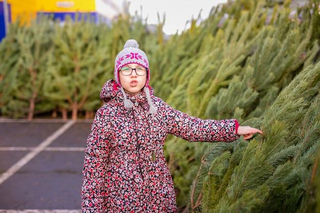 Criança, escolhendo e decorando uma árvore de natal Foto Premium