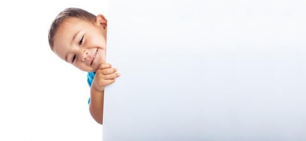 Criança escondendo atrás de um cartaz branco Foto gratuita