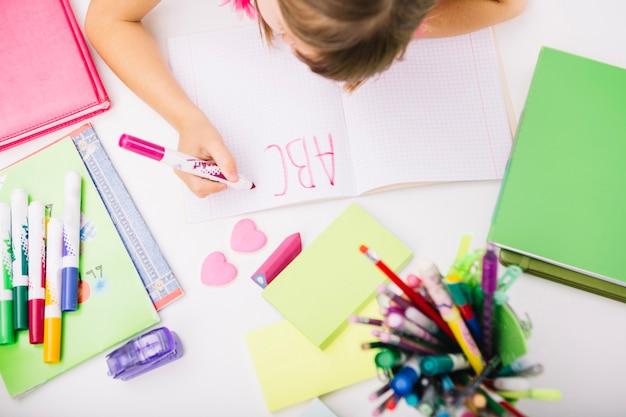 Criança escrevendo letras no bloco de notas Foto gratuita