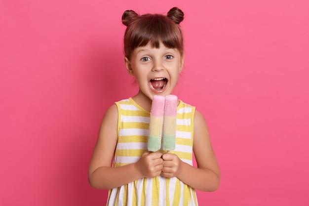 Criança europeia pequena mordendo sorvete de frutas, menina encantadora com a boca bem aberta, vestindo roupas de verão, parece feliz, se divertindo com uma sobremesa deliciosa. Foto gratuita