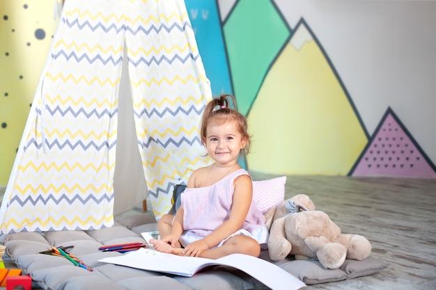 Criança faz lição de casa. criança desenha no jardim de infância. pré-escolar aprende a escrever e ler. garoto criativo. menina desenha com lápis em um álbum em casa. conceito de infância e desenvolvimento infantil Foto Premium