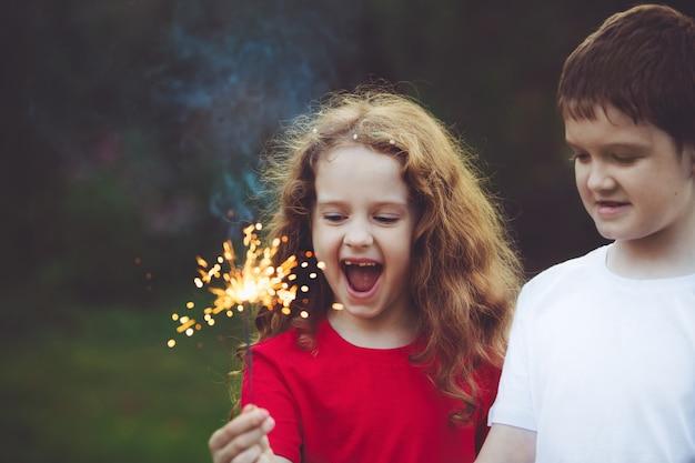 Criança feliz amigo na festa com queimando diamante na mão. Foto Premium