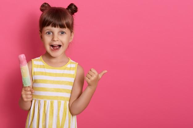 Criança feliz animada com sorvete com a boca amplamente aberta, apontando o polegar de lado, engraçadinha com nodos, copie o espaço para propaganda. Foto gratuita
