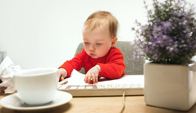 Criança feliz bebê menina criança sentada com o teclado do computador isolado Foto gratuita