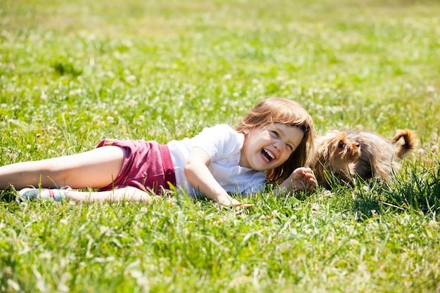 Criança feliz brincando com cachorro no prado no verão Foto gratuita