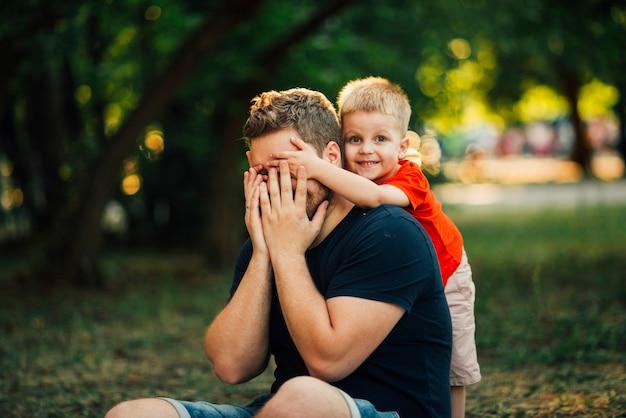 Criança feliz, cobrindo os olhos do pai Foto gratuita