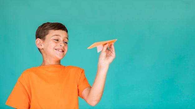 Criança feliz com avião de papel com espaço de cópia Foto gratuita