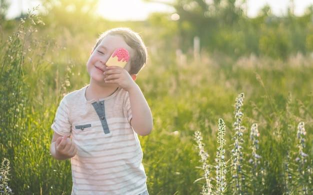 Criança feliz comendo biscoitos em forma de sorvete Foto Premium