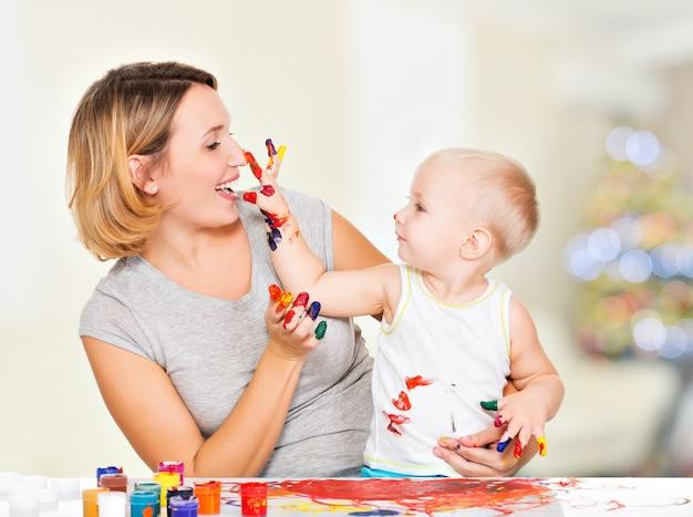 Criança feliz desenha no rosto de sua mãe em casa. Foto gratuita