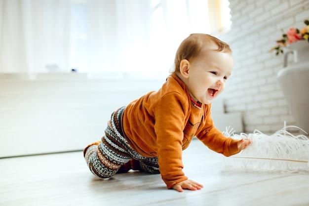 Criança feliz em suéter de laranja joga com pena no chão Foto gratuita