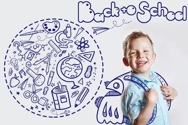 Criança feliz em uma camisa leve vai para a escola pela primeira vez. atrás dele é uma mochila em que uma variedade de ícones Foto Premium