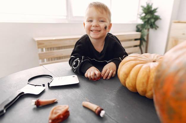 Criança feliz na festa de halloween. divertir-se com as crianças dentro de casa. bby vestindo uma fantasia. conceito de crianças prontas para uma festa. Foto gratuita