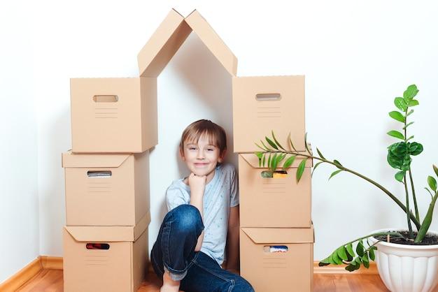 Criança feliz na nova casa. hospedando uma jovem família com criança. a família muda-se para um novo apartamento. menino brincando em seu novo apartamento. gracinha, ajudando a desempacotar as caixas. Foto Premium
