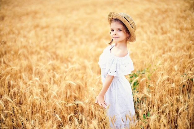 Criança feliz no campo de trigo outono. menina bonita no vestido branco e chapéu de palha divirta-se com a brincar, a colheita Foto Premium