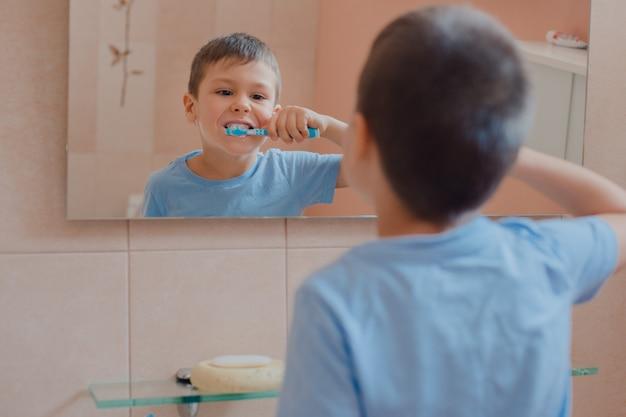 Criança feliz ou criança escovando os dentes no banheiro. Foto Premium
