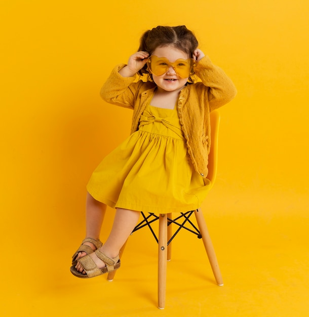 Criança feliz posando enquanto usava óculos de sol Foto gratuita