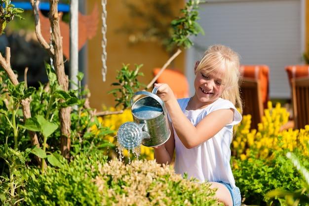 Criança feliz, regando flores Foto Premium
