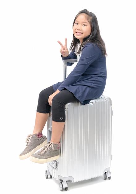 Criança feliz viajante sentar na bagagem isolada Foto Premium