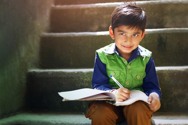 Criança indiana, escrevendo no caderno Foto Premium