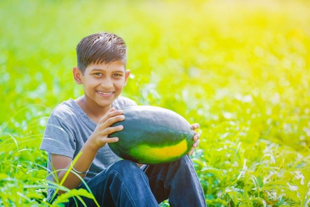 Criança indiana no campo de melancia Foto Premium