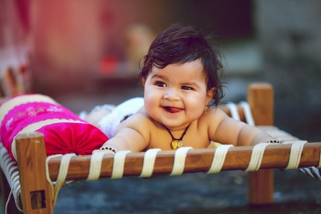 Criança indiana pequena bonito sorrir e brincar na cama de madeira Foto Premium