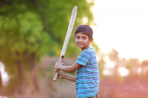 Criança indiana rural jogando críquete Foto Premium