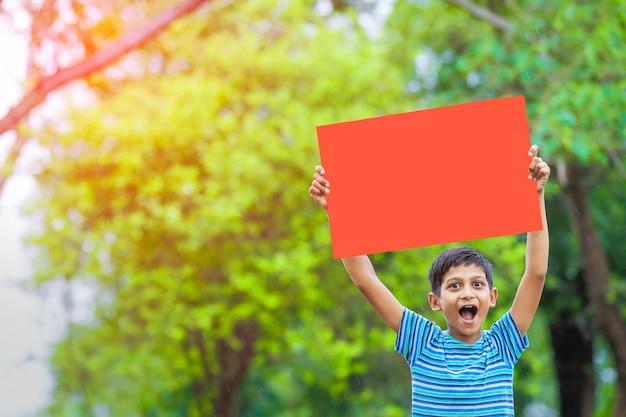 Criança indiana segurando cartaz vazio Foto Premium