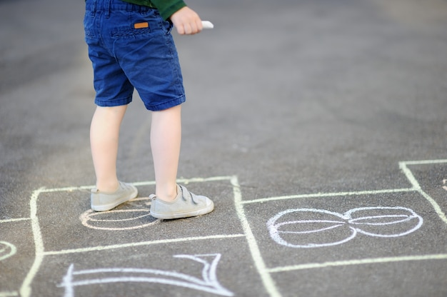 Criança, jogo amarelinha, jogo, ligado, pátio recreio, ao ar livre, ligado, um, dia ensolarado Foto Premium