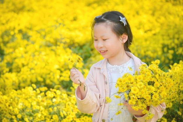 Criança linda menina asiática segurando flores e sorrisos no campo de crisântemo amarelo. Foto Premium