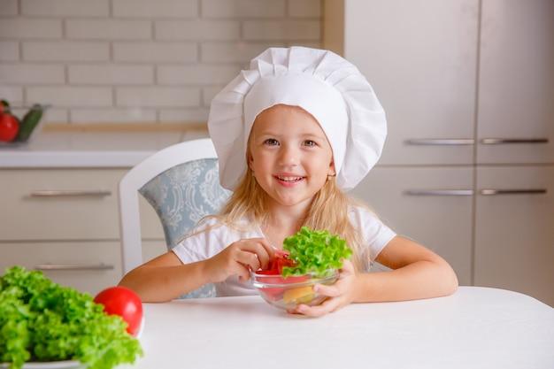 Criança loira no chapéu de um chef na cozinha comendo legumes Foto Premium