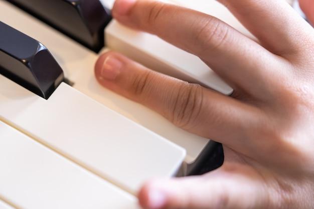 Criança mãos nas teclas de piano praticando música Foto Premium