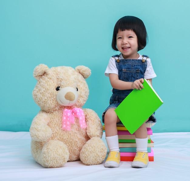Criança menina ou uma menina bonita lendo um livro e sentado nos livros com um brinquedo Foto Premium
